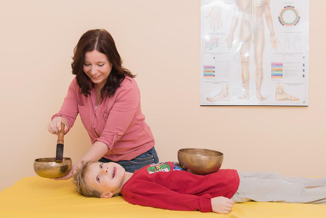 Foto: Melanie behandelt ein Kind mit Klangschalen.