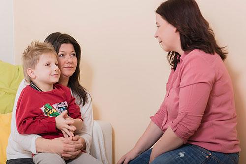 Foto: Klientin mit Kind am Schoß im Gespräch mit Melanie